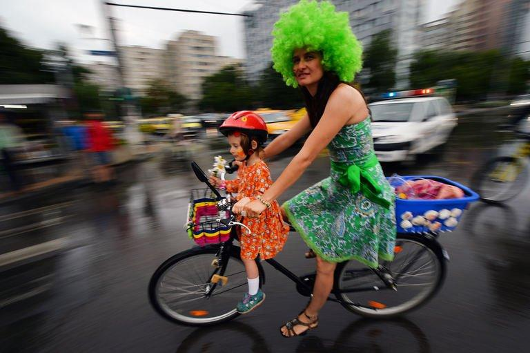 """A woman rides a bike with her daughter during the third """"SkirtBike"""" in Bucharest on June 2, 2013. More than 1,500 Romanian women in colourful skirts and high heels cycled through the country's main cities to promote urban biking as a """"stylish and fun"""" way of transport"""