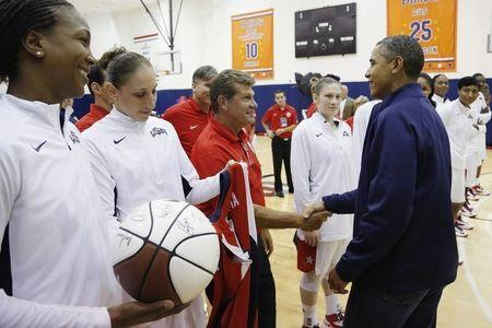 U.S. President Barack Obama (R) greets (L-R) Tamika Catchings, Diana Taurasi, and coach Geno Auriemma of the U.S. Olympic women's basketball team after their exhibition game against Brazil in Washington, July 16, 2012. REUTERS/Jonathan Ernst