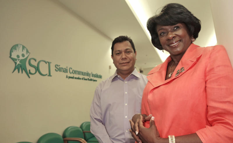 From left, Raul Garcia, Multicultural Community Affairs Manager, and Debra Wesley, President of the Sini Community Institute stands in the facility's lobby Thursday, Aug. 15, 2013, in Chicago. Sinai Health System in Chicago is one of more than 100 U.S. organizations awarded federal Navigator grants Thursday to help consumers sign up for health insurance. Sinai's community-based corporation, the Sinai Community Institute, plans to operate a navigator program together with a consortium of public and community and faith-based organizations. Sinai is getting $157,271. (AP Photo/M. Spencer Green)