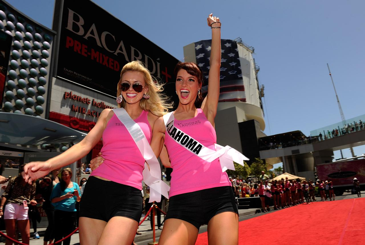 LAS VEGAS, NV - MAY 22:  Miss USA 2012 contestants Miss Missouri Katie Kearney (L) and Miss Oklahoma Lauren Lundeen celebrate after competing in the Miss USA 2012 Wedge Run on the Las Vegas Strip at the Planet Hollywood Resort & Casino on May 22, 2012 in Las Vegas, Nevada.  (Photo by David Becker/Getty Images For Chinese Laundry)