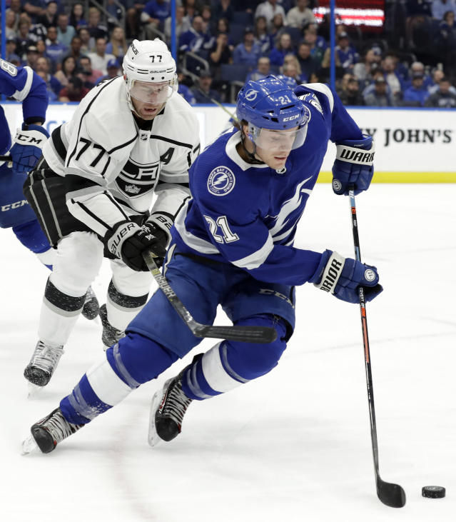 Tampa Bay Lightning center Brayden Point (21) gets around Los Angeles Kings center Jeff Carter (77) during the first period of an NHL hockey game Monday, Feb. 25, 2019, in Tampa, Fla. (AP Photo/Chris O'Meara)