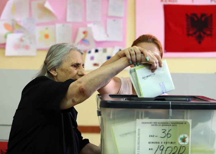 An Albanian woman casts her vote in Tirana, Sunday, June 23, 2013 in the Albanian elections. An Albanian political candidate was shot and a supporter of a rival party killed in an exchange of gunfire near a polling station, police said Sunday, as the country held crucial elections already marred by a dispute that could leave the outcome up in the air. Both conservative Prime Minister Sali Berisha and his close rival, Socialist leader Edi Rama, have hopes for eventual entry to the European Union, and the election is seen as a test of whether the country can run a fair and safe vote. (AP Photo/Hektor Pustina)