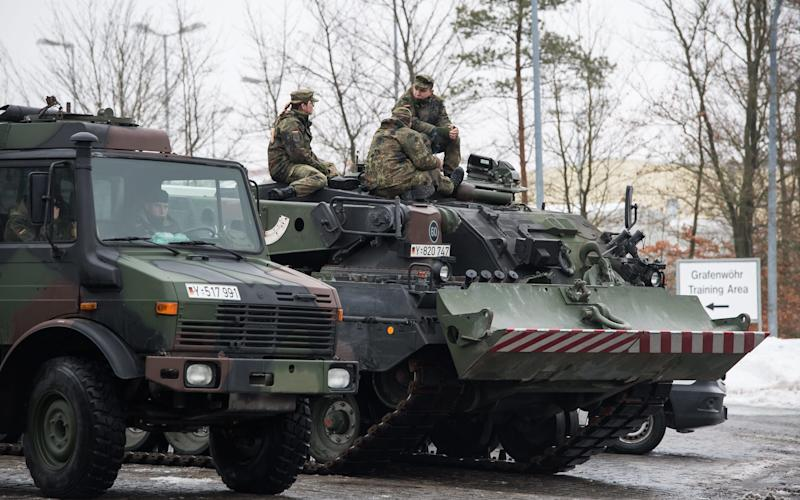 German Bundeswehr Soldiers of the 'battalion of armored infantryman' called 'Panzergrenadierbataillon 122' sit on a wrecker called 'Bueffel' during vehicles wait to be loaded onto a train in Grafenwoehr, Germany, 31 January 2017, before being deployed as part of a NATO force in Lithuania - Credit: LUKAS BARTH