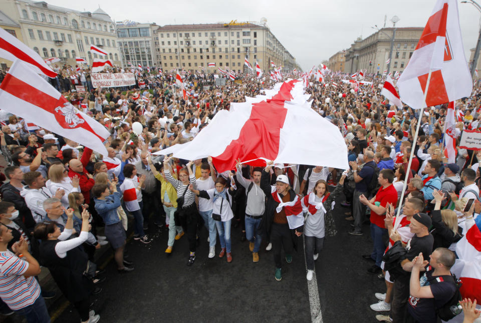 FILE - In this Aug. 23, 2020, file photo, demonstrators carry an opposition flag at a protest at Independence square in Minsk, Belarus. Raman Pratasevich, a dissident journalist who ran a channel on a messaging app used to organize demonstrations against the iron-fisted rule of President Alexander Lukashenko, left Belarus in 2019 to try to escape the reach of the authorities, but he was arrested on Sunday, May 23, 2021, when the jet he was traveling on from Greece to Lithuania was diverted to Minsk by Belarusian flight controllers who said there was a bomb threat against the plane. (AP Photo/File)