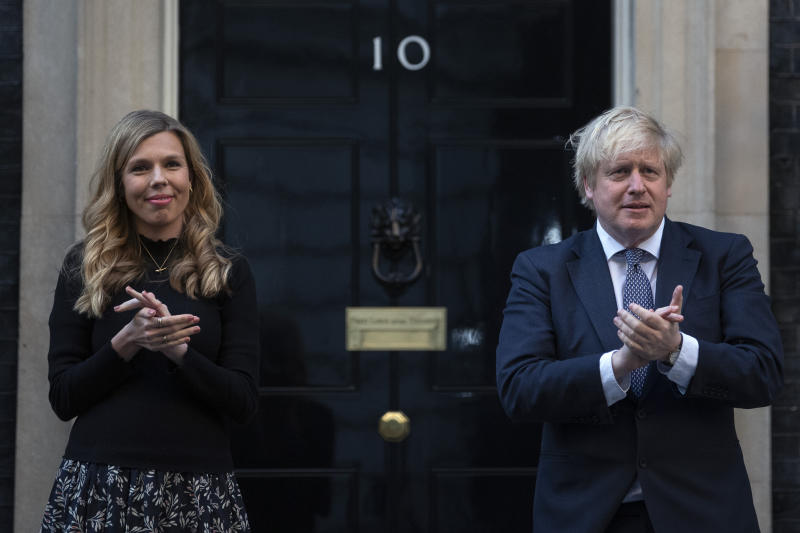 Prime Minister Boris Johnson and Carrie Symonds stand in Downing Street, London, to join in the applause to salute local heroes during Thursday's nationwide Clap for Carers to recognise and support NHS workers and carers fighting the coronavirus pandemic. (Photo by Victoria Jones/PA Images via Getty Images)
