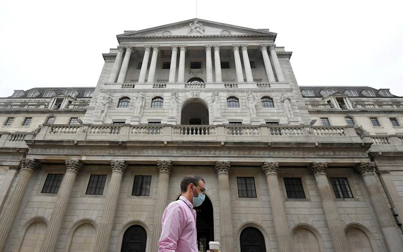 A man wearing a protective face mask walks past the Bank of England in the City of London, Britain, August 6 - Toby Melville/Reuters