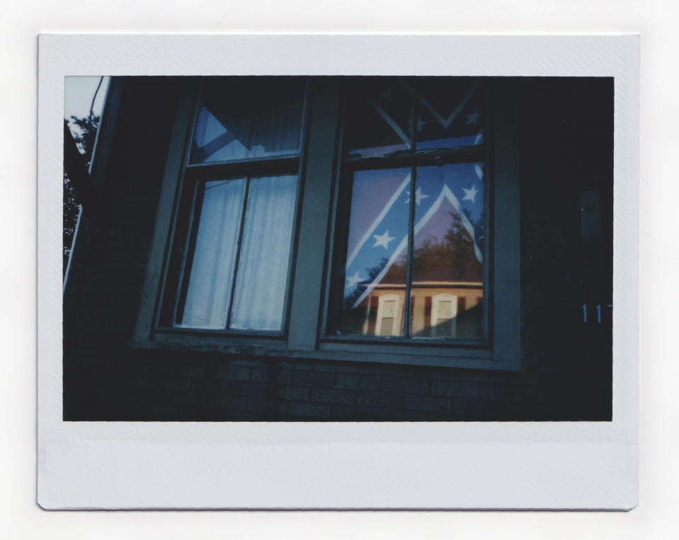 """A Confederate flag hangs in the window of a home of a young Black woman in Shawnee Ohio, on Tuesday, July 28, 2020. Confederate flags have become a symbol of a certain America: white, often rural, sometimes southern, normally conservative. This time, though, it turned out to be a young Black woman who was flying it. She said it was her way of """"giving the finger"""" to everyone, including white Southerners who believe they control the flag and its symbolism. (AP Photo/Wong Maye-E)"""