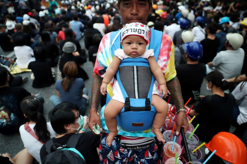 A vendor carrying a baby sells cool drinks during a protest in Bangkok