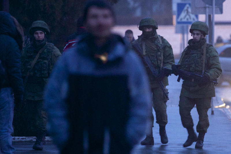 Unidentified armed men patrol a square in front of the airport in Simferopol, Ukraine, Friday, Feb. 28, 2014. Dozens of armed men in military uniforms without markings occupied the airport in the capital of Ukraine's strategic Crimea region.(AP Photo/Ivan Sekretarev)