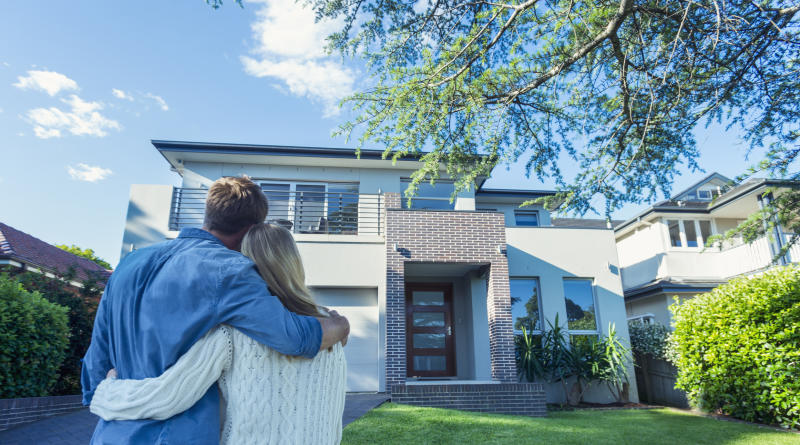 Couple standing in front of their new home. Source: Getty
