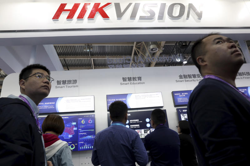 In this photo taken Tuesday, Oct. 23, 2018, visitors past by a booth for state-owned surveillance equipment manufacturer Hikvision at the Security China 2018 expo in Beijing, China. The Chinese video surveillance company says it is taking concern about the use of its technology seriously following a report that the U.S. may block several Chinese surveillance companies from buying American components. (AP Photo/Ng Han Guan)