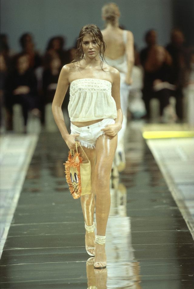 A model on the runway at the Spring/Summer 2000 Chloé ready-to-wear collection designed by Stella McCartney, wearing white tube top with smocking at top edge, fringed hot pants, high-heel sandals with white and gold ankle bands, and carrying a straw bag with cat-face design. (Photo: Getty Images)
