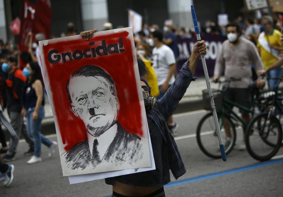 A protester holds a poster depicting Brazilian President Jair Bolsonaro as Adolf Hitler and the Portuguese word for genocidal, during a demonstration against Bolsonaro's handling of the coronavirus pandemic and economic policies protesters say harm the interests of the poor and working class, in Rio de Janeiro, Brazil, Saturday, June 19, 2021. Brazil is approaching an official COVID-19 death toll of 500,000 — second-highest in the world. (AP Photo/Bruna Prado)