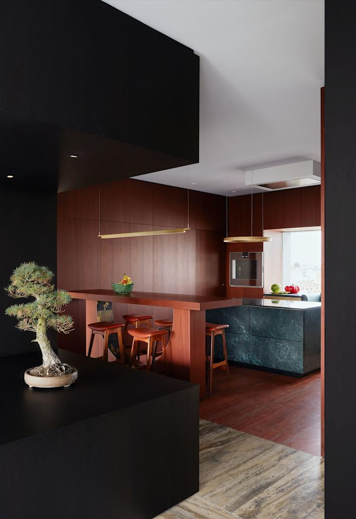 """<div class=""""caption""""> The kitchen has a red travertine floor, which complements the silver travertine used on the hallway floor. The bar light fixture has semicircular elements, referencing the large curved windows of the façade. The bar stools are vintage midcentury pieces. </div>"""