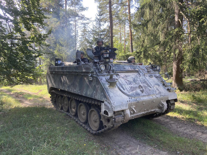 Image: An M113 armored personnel carrier driven by U.S. soldiers, pretending to be anti-NATO forces, participates in a woodland exercise focused on targeting Ukrainian soldiers at the Hohenfels training area in southern Germany. (Edward Kiernan / NBC News)