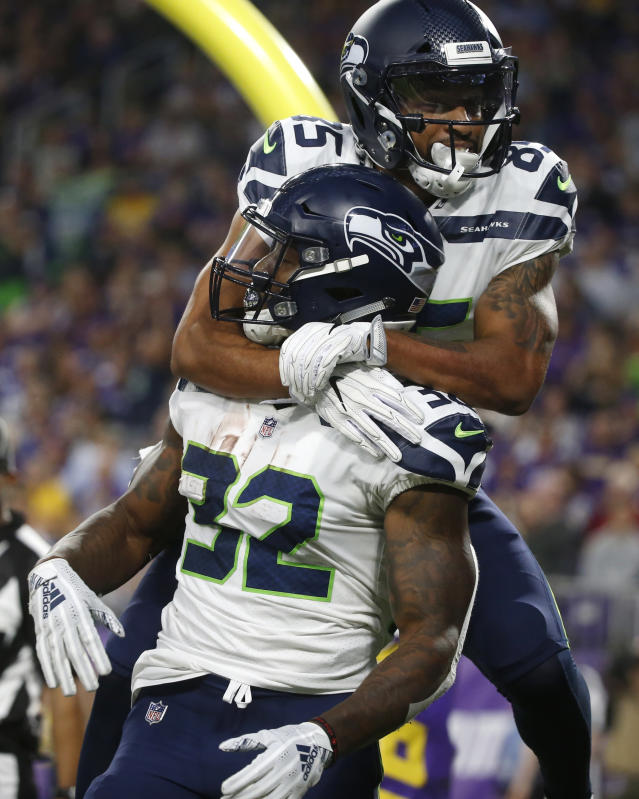 Seattle Seahawks running back Chris Carson (32) celebrates with teammate Keenan Reynolds after scoring on a 6-yard touchdown run during the first half of an NFL preseason football game against the Minnesota Vikings, Friday, Aug. 24, 2018, in Minneapolis. (AP Photo/Bruce Kluckhohn)