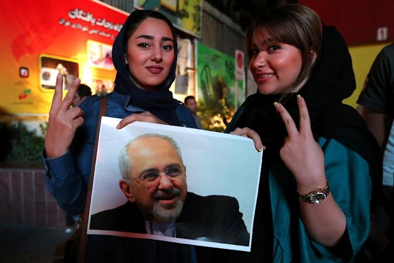 Iranian women hold a portrait of Foreign Minister Mohammad Javad Zarif during celebrations in northern Tehran on July 14, 2015, after Iran's nuclear negotiating team struck a deal with world powers (AFP Photo/Atta Kenare)