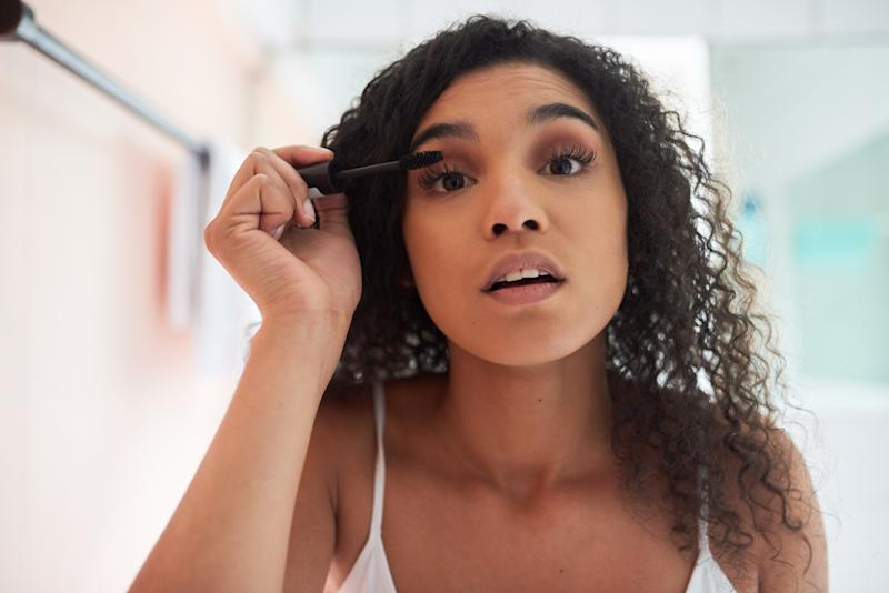 Portrait of an attractive young woman applying mascara in the bathroom