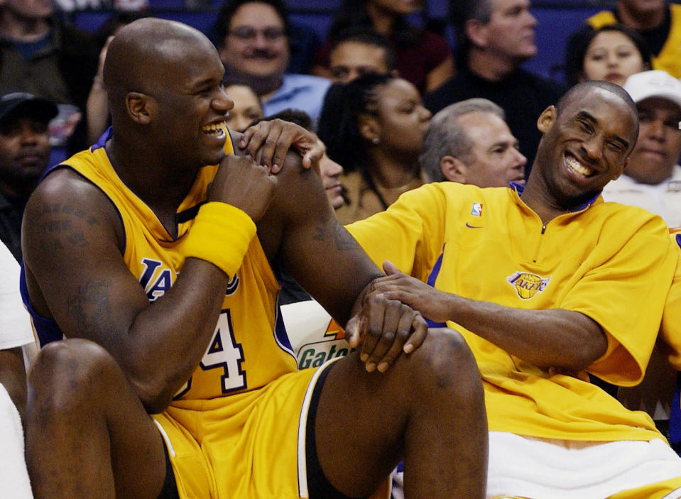Los Angeles Lakers Shaquille O'Neal, left, and Kobe Bryant share a laugh on the bench while their teammate take on the Denver Nuggets during the fourth quarter at Staples Center in Los Angeles, April 15, 2003. Bryant, the 18-time NBA All-Star who won five championships and became one of the greatest basketball players of his generation during a 20-year career with the Los Angeles Lakers, died in a helicopter crash Sunday, Jan. 26, 2020. (AP Photo/Kevork Djansezian)