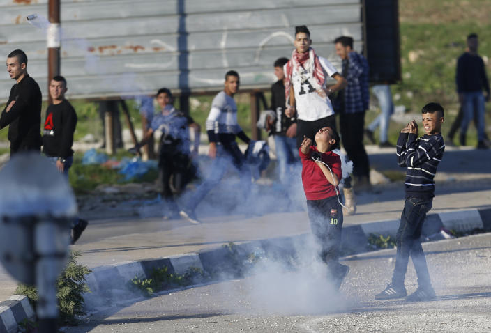 Palestinian protestor throws back a teargas canister during clashes with Israeli troops at the Hawara checkpoint, south of the West Bank city of Nablus, Friday, Dec. 14, 2018. (AP Photo/Majdi Mohammed)