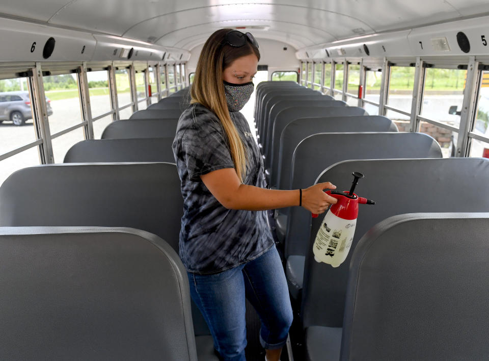 Robeson Township, PA - August 5: School Bus Driver Jennifer Simcox on a bus with the pump spray bottle of disinfectant each bus driver will have to disinfect their busses. At Eshelman Transportation in Robeson Township Wednesday afternoon August 5, 2020 where they are preparing their bus drivers for the start of the school year and new precautions during the coronavirus / COVID-19 pandemic.  (Photo by Ben Hasty/MediaNews Group/Reading Eagle via Getty Images)