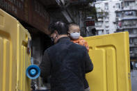 A child is carried between yellow barriers used to seal off a neighborhood in Wuhan in central China's Wuhan province on Wednesday, April 1, 2020. Skepticism about China's reported coronavirus cases and deaths has swirled throughout the crisis, fueled by official efforts to quash bad news in the early days and a general distrust of the government. In any country, getting a complete picture of the infections amid the fog of war is virtually impossible. (AP Photo/Ng Han Guan)