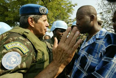 FILE PHOTO: Brazilian General Augusto Heleno Periera (L) talks to the leader of a group of supporters of former Haitian President Jean-Bertrand Aristide about the route they should take before a demonstration by several thousand Arsitide supporters held on March 29, 2005, the 18th anniversary of the country's constitution, in Port-au-Prince, Haiti REUTERS/Daniel Morel/File photo