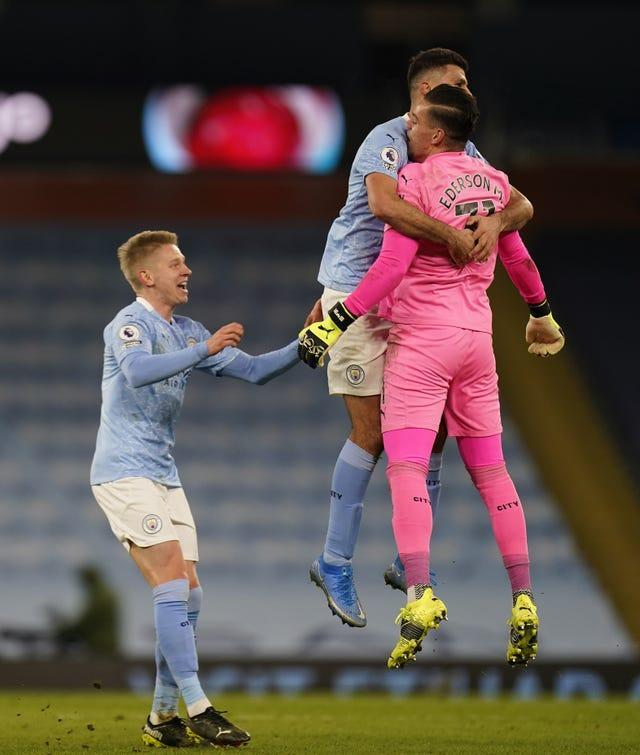 Manchester City goalkeeper Ederson (right) is congratulated by team-mates Joao Cancelo (centre) and Oleksandr Zinchenko after setting up Ilkay Gundogan to score