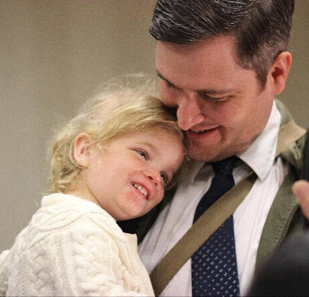Nicholas J. Van Sickels stands with his husband, Andrew S. Bond, not seen, and holds their adopted daughter, Jules, 2, before a news conference in New Orleans about a federal lawsuit filed Wednesday, Feb. 12, 2014, to challenge the Louisiana Constitution's ban on recognizing same-sex marriages performed in states where they are legal. They are among four couples, all married states where same-sex marriage is legal, who joined the Forum for Equality Louisiana in a suit against the state registrar and state revenue secretary. (AP Photo/Janet McConnaughey)