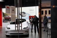 People wear protective face masks, as the global outbreak of the coronavirus disease (COVID-19) continues, inside a Tesla showroom in Chicago