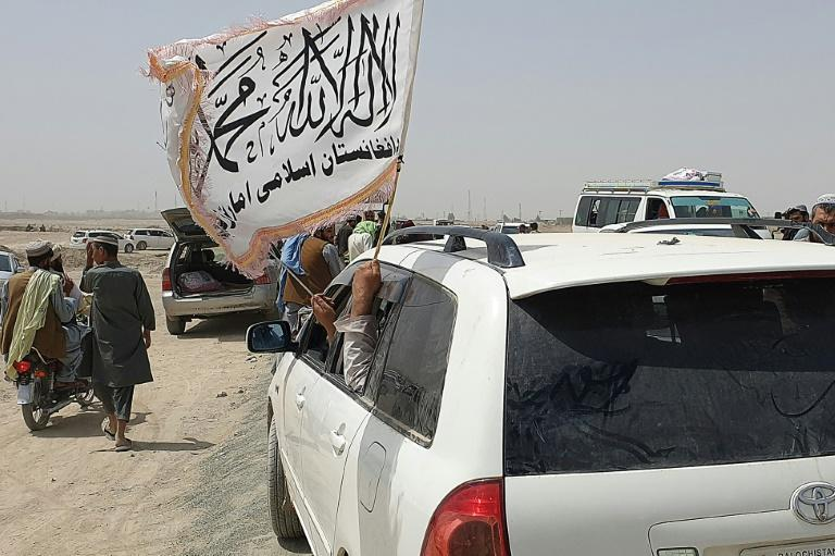 Taliban supporters on the Pakistan side of the border waved flags after hearing the Afghan frontier town had fallen to the insurgents