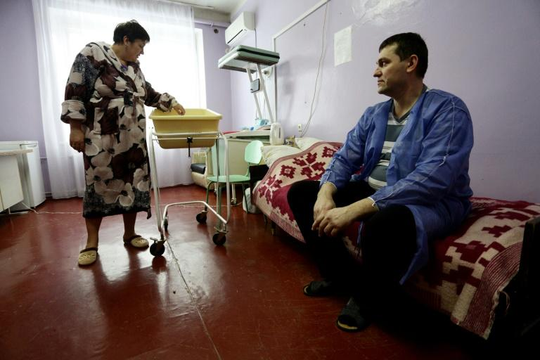 Ukranian woman Olena Gorbatova (L), plays with her baby as her husband Sergiy (R) looks on at the maternity hospital in the war-torn eastern city of Avdiivka