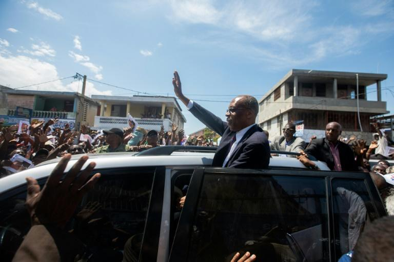 Former Haitian president Jean-Bertrand Aristide greets supporters in Port-au-Prince in a rare public outing to testify in a money laundering case