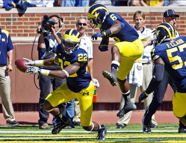 Michigan safety Jarrod Wilson (22) celebrates with defensive back Raymon Taylor (6) after intercepting an Akron pass in the end zone in the fourth quarter of an NCAA college football game in Ann Arbor, Mich., Saturday, Sept. 14, 2013. Michigan won 28-24. (AP Photo/Tony Ding)