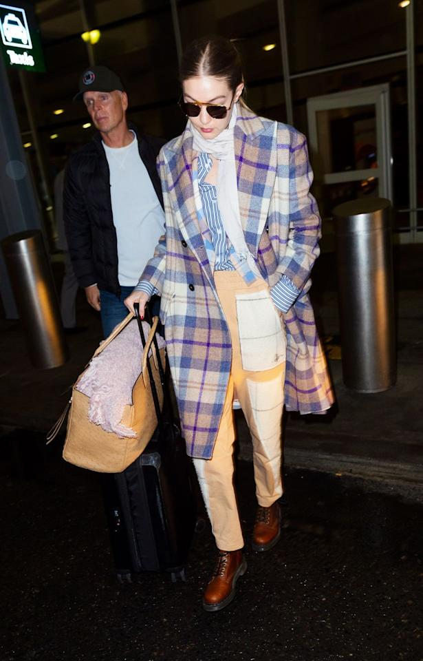 <p>Mad about plaid, Gigi travels in style. The model is seen leaving JFK airport wearing a Vivienne Westwood coat and a Ferragamo bag. </p>