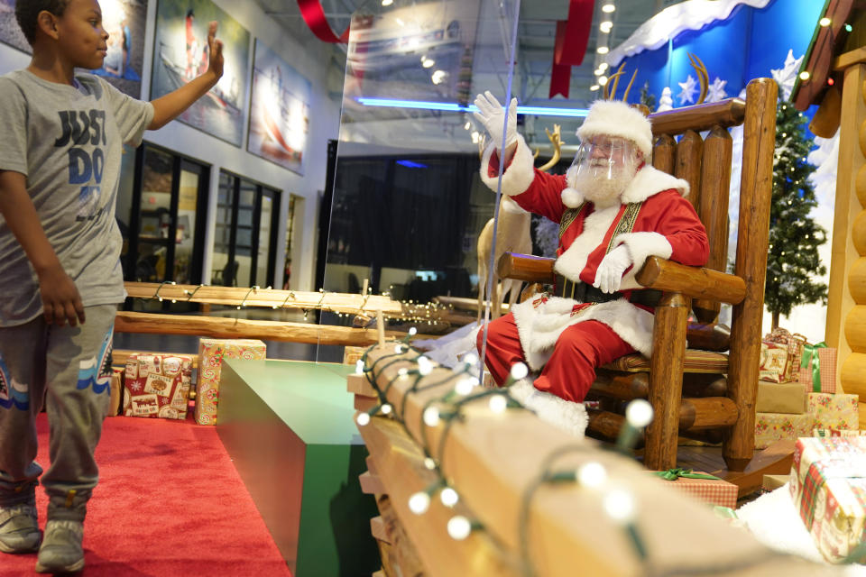 Jayden Dicks, 6, waves to Santa from the other side of a transparent barrier at a Bass Pro Shop in Bridgeport, Conn., Tuesday, Nov. 10, 2020. Malls are doing all they can to keep the jolly old man safe from the coronavirus, including banning kids from sitting on his knee, completely changing what a Santa visit looks like. (AP Photo/Seth Wenig)