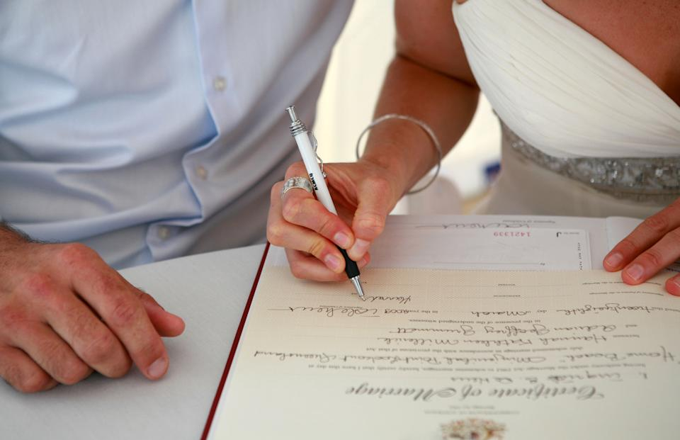 newlyweds signing marriage certificate stock photo