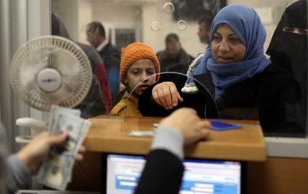 A Palestinian Hamas-hired civil servant receives her salary paid by Qatar in Khan Younis in the southern Gaza Strip