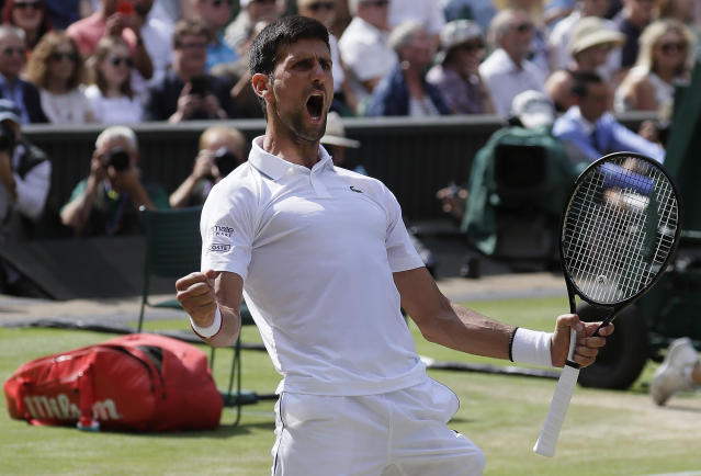 Serbia's Novak Djokovic celebrates after beating Spain's Roberto Bautista Agut in a Men's singles semifinal match on day eleven of the Wimbledon Tennis Championships in London, Friday, July 12, 2019. (AP Photo/Kirsty Wigglesworth)