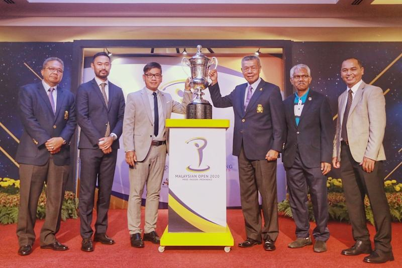 Malaysian Golf Association President Tan Sri Mohd Anwar Mohd Nor and Kota Permai Golf and Country Club Direct of Club Operations, Township and Property Management Tang Meng Loon lift the trophy together with partners after the ceremony December 16, 2019. — Picture by Ahmad Zamzahuri