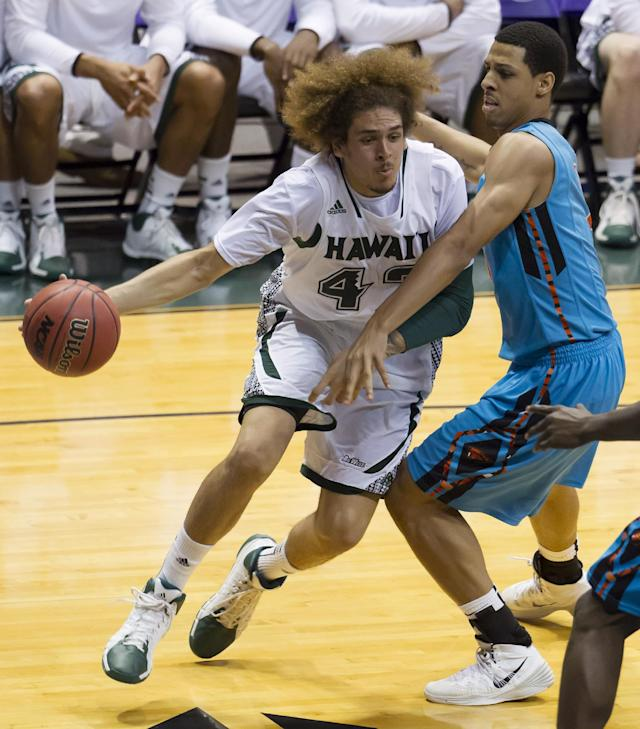 Hawaii forward Isaac Fotu, left, drives the baseline while being defended by Oregon State guard Victor Robbins, right, during the second half of an NCAA college basketball game at the Diamond Head Classic on Wednesday, Dec. 25, 2013, in Honolulu. Hawaii won 79-73. (AP Photo/Eugene Tanner)