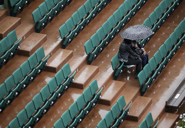Spectators protect themselves from the rain with umbrella before the start of the women's quarter-final match between Svetlana Kuznetsova of Russia and Simona Halep of Romania during the French Open tennis tournament at the Roland Garros stadium in Paris June 4, 2014. REUTERS/Stephane Mahe (FRANCE - Tags: SPORT TENNIS ENVIRONMENT)
