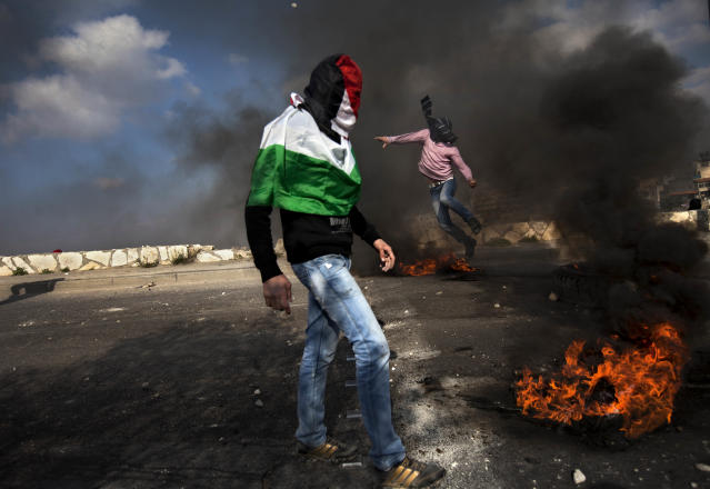 "<p>Masked Palestinians clash with Israeli troops as they mark the ""Land Day"" in the east Jerusalem neighborhood of Issawiyeh on March 30, 2012. (Photo: Oded Balilty/AP) </p>"