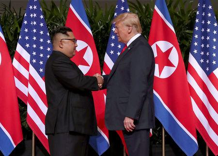 FILE PHOTO - U.S. President Donald Trump shakes hands with North Korean leader Kim Jong Un at the Capella Hotel on Sentosa island in Singapore