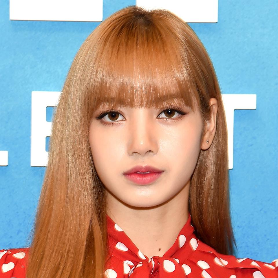 "For her first-ever NYFW appearance, <a rel=""nofollow"" href=""https://www.allure.com/story/lisa-blackpink-paper-clip-hair-k-pop?mbid=synd_yahoo_rss"">Lisa of beloved Korean girl group Blackpink</a> brought classic K-pop style and her signature sleek, blunt bangs. To complement her dewy, <a rel=""nofollow"" href=""https://www.allure.com/story/how-to-get-glass-skin-korean-beauty?mbid=synd_yahoo_rss"">glass-like skin</a>, she swiped an <a rel=""nofollow"" href=""https://www.allure.com/story/k-beauty-best-nude-lip-tints-reddit?mbid=synd_yahoo_rss"">MLBB stain</a> onto her lips, defined her eyes with subtle feline flicks, and coated her lashes with lots of mascara for a separated, doll-like effect. Lisa's lower lids were also highlighted with a shimmery bronze shadow to bring even more radiance to the look."