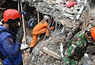 Rescuers search for survivors in a collapsed building in Mamuju city after a 6.2-magnitude quake hit the Indonesian island of Sulawesi