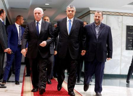 Egyptian intelligence chief Khaled Fawzi (C) walks with head of Hamas delegation Saleh Arouri and Fatah leader Azzam Ahmad as they sign a reconciliation deal in Cairo, Egypt, October 12, 2017. REUTERS/Amr Abdallah Dalsh