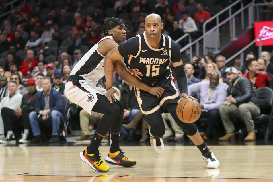 Atlanta Hawks guard Vince Carter (15) drives on Los Angeles Clippers guard Terance Mann (14) in the first half of an NBA basketball game Wednesday, Jan. 22, 2020, in Atlanta, Ga. (AP Photo/Brett Davis)