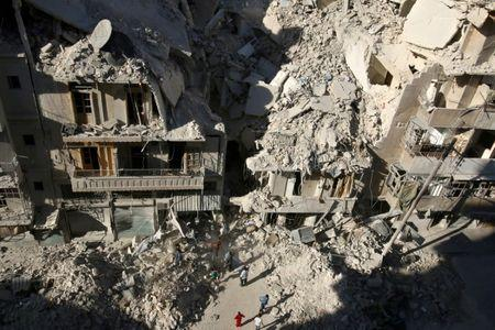 FILE PHOTO: People dig in the rubble in an ongoing search for survivors at a site hit previously by an airstrike in the rebel-held Tariq al-Bab neighborhood of Aleppo