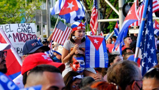Protesters in Miami wave Cuban and American flags.